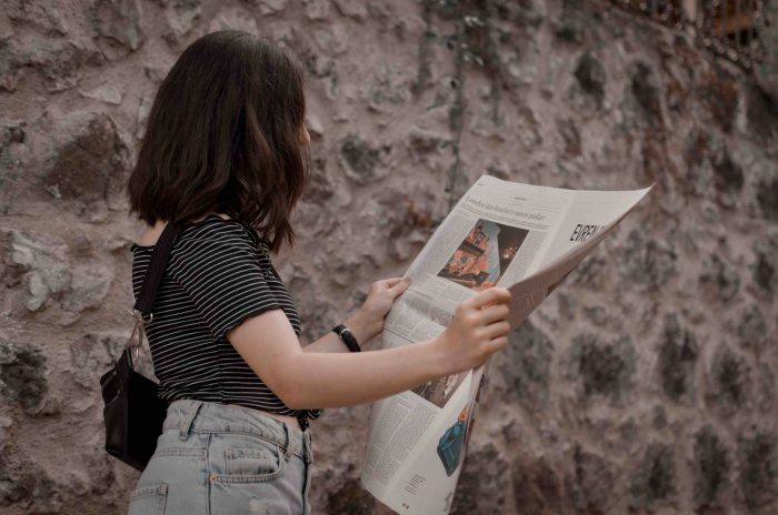 A young woman reading a newspaper with attention grabbing headlines.